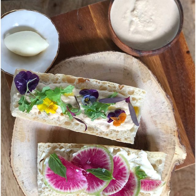 Smoked butter on sliced baguette topped with radishes and edible pansies